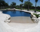 Travertine Decking, Beach Entry with Gold Pebble, Midnight Blue Pebble, Elevated Spa, Travertine Stairstepped Spillway